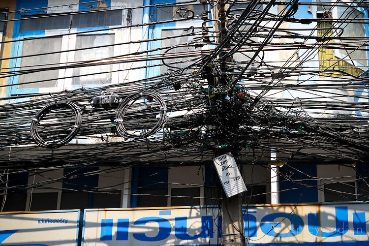 Overwhelmingly confused mix of electrice wires on the streets of Bangkok, Thailand.
