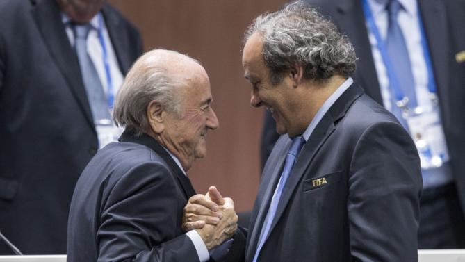 FIFA president Sepp Blatter after his election as President greeted by UEFA President Michel Platini, right, at the Hallenstadion in Zurich, Switzerland, Friday, May 29, 2015. Blatter has been re-elected as FIFA president for a fifth term, chosen to lead world soccer despite separate U.S. and Swiss criminal investigations into corruption. The 209 FIFA member federations gave the 79-year-old Blatter another four-year term on Friday after Prince Ali bin al-Hussein of Jordan conceded defeat after losing 133-73 in the first round. (Patrick B. Kraemer/Keystone via AP)